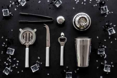 Bartender equipment set with shaker and stainer and ice cubes on black background top-down pattern. 스톡 콘텐츠