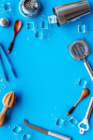 Bar utensil, tools - shaker, stainer - near ice cubes on blue background top-down.