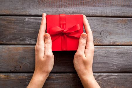 Give a gift on Valentine's Day. Women hand hold beautiful red present box on dark wooden background top-down. Foto de archivo - 138467722