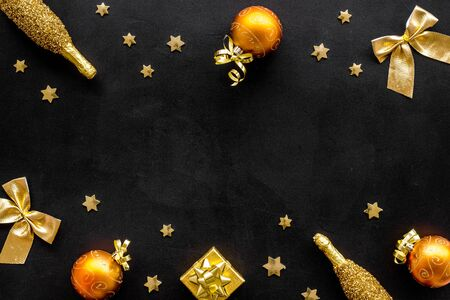New Year mockup in gold color. Champagne bottle, present box, decoration, balls on black background top-down frame copy space