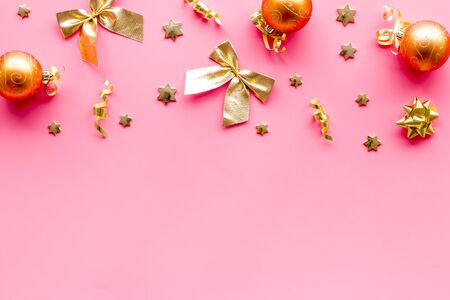 New Year decoration background - golden balls and bows on pink desk top-down frame.