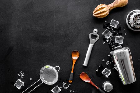 Bar utensil, tools - shaker, stainer - near ice cubes on black background top-down frame copy space