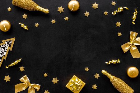 New Year mockup in gold color. Champagne bottle, present box, decoration, balls on black background top-down frame. Zdjęcie Seryjne