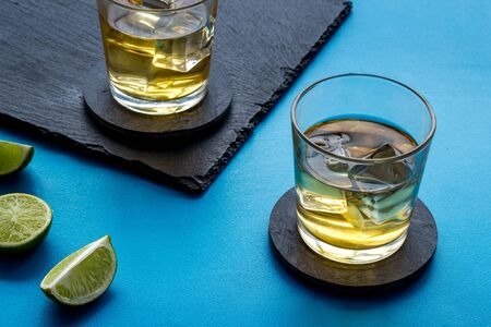 Whiskey with ice. To glasses of strong alcohol drink near lime on blue background. 스톡 콘텐츠