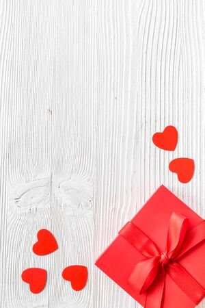 Gift to a sweetheart on Valentine's Day. Red present box near hearts on white wooden background top-down. Foto de archivo - 138467135
