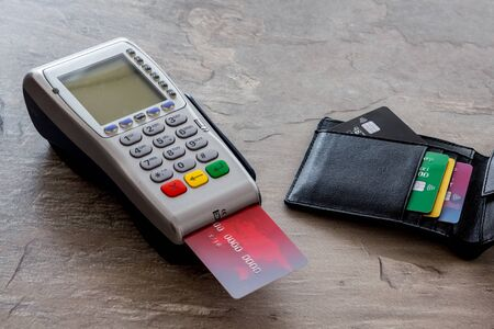 Bank terminal for payments and plastic card on grey stone background.
