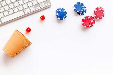 Hazard gemes online concept. Poker chips, dices, cup for dice near keyboard on white background top-down.