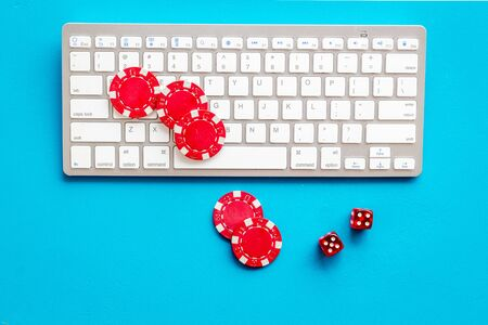 Gambling, online games. Chips and dices near keyboard on blue background top-down.