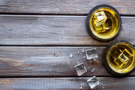 Whiskey near ice cubes on dark wooden background top-down. 스톡 콘텐츠