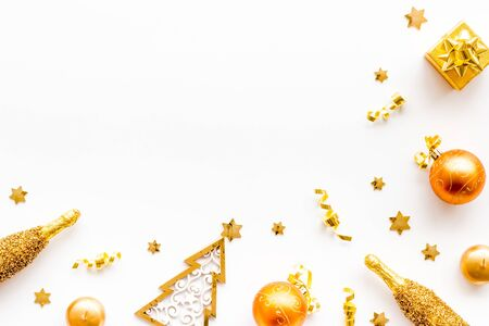 New Year symbols - tree, champagne, decorations - on white background top-down frame.