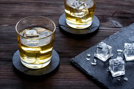 Whiskey near ice cubes on dark wooden background. 스톡 콘텐츠