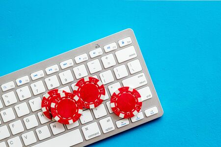Online poker. Chips near keyboard on blue background top-down. Banque d'images