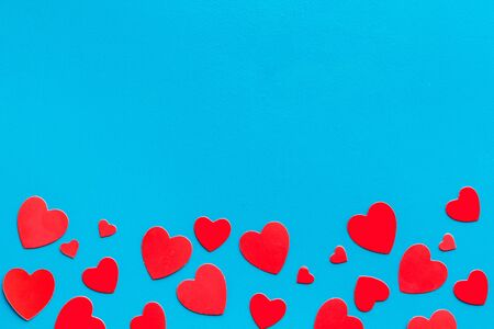 Valentine's Day design. Red hearts frame on blue background top-down.