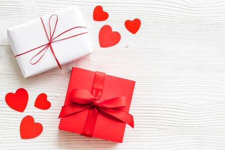 Present to a lover on Valentine's Day. Gift boxes near paper hearts on white wooden background top-down Foto de archivo - 138467417
