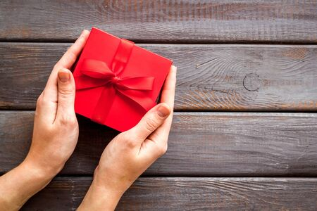 Give a gift on Valentine's Day. Women hand hold beautiful red present box on dark wooden background top-down. Foto de archivo - 138467587