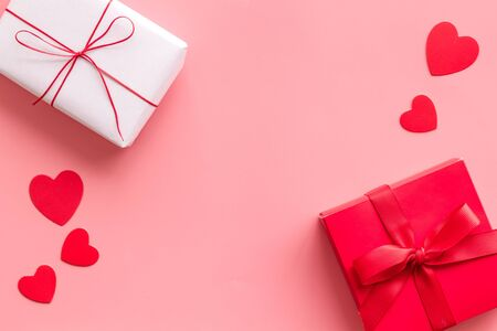 Present to a lover on Valentine's Day. Gift boxes near paper hearts on pink background top-down. Foto de archivo - 138468461