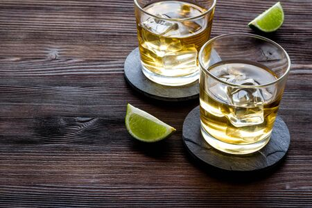 Whiskey with ice. To glasses of strong alcohol drink near lime on dark wooden background.