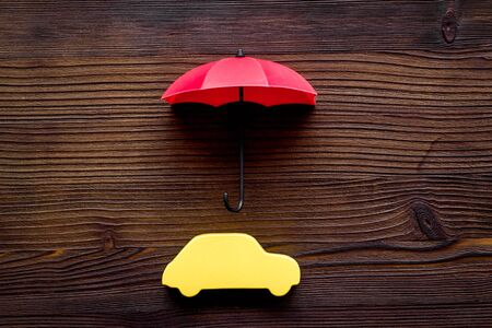Car protection. Automobile toy under umbrella on dark wooden background top-down copy space