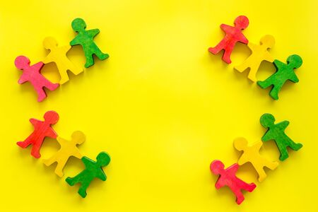 Team work, teambuilding concept. People cutouts on yellow background top-down copy space