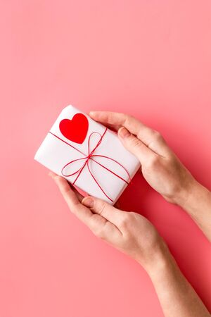 Give a gift on Valentine's Day. Women hand hold present box decorated with small heart on pink background top-down. Foto de archivo - 138468487