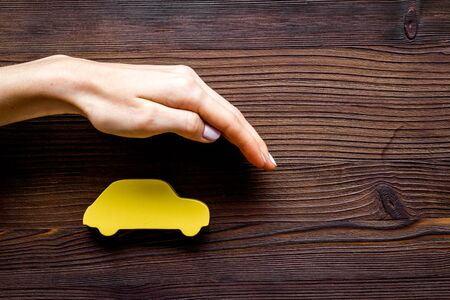 Car insurance. Hand defends automobile cutout on dark wooden background top-down copy space