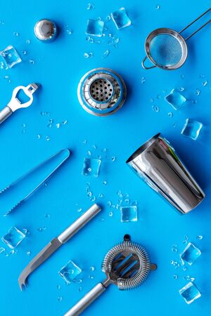 Bartender equipment set with shaker and stainer and ice cubes on blue background top-down pattern.