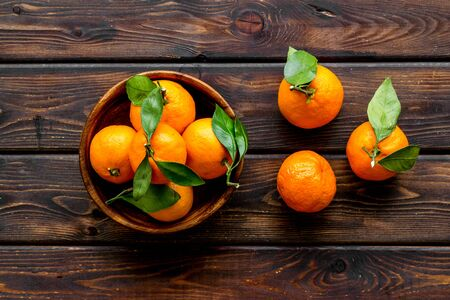 Ripe tangerines on dark wooden table. Citruses with green leaves in bowl top-down
