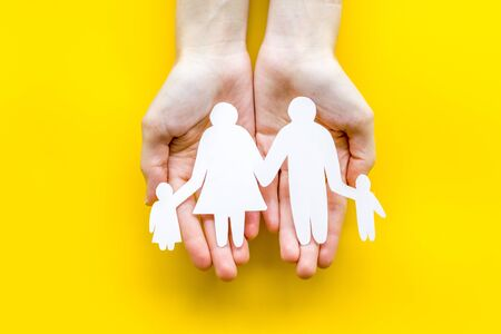 Live insurance concept. Family silhouette on palms on yellow background top-down