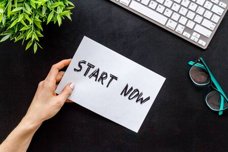 Start now. Motivative text on black office desk top-down