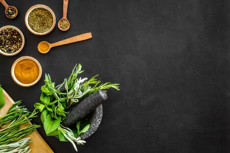 Herbs and spices on black kitchen desk top-down.