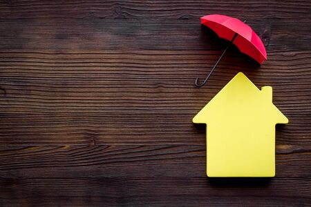 House insurance concept. Toy house defended by umbrella on dark wooden backgound top view copy space