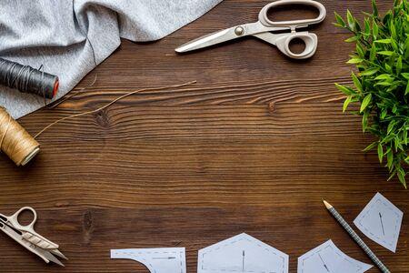 Sewing wokrshop. Textile, pattern, scissors, thread on dark wooden background top-down.