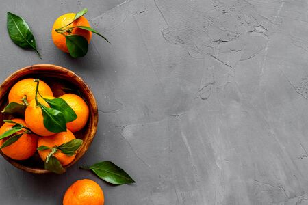 Ripe tangerines on grey table. Citruses with green leaves in bowl top-down.