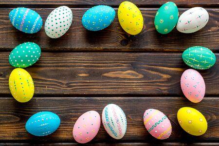 Cornice colorata delle uova di Pasqua su fondo di legno scuro dall'alto verso il basso.