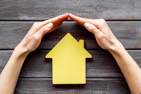 Property insurance concept. Hand defends house cutout on dark wooden backgound top view.