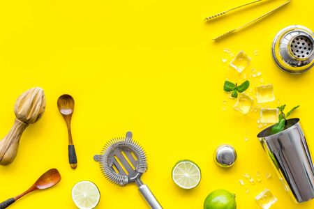 Bar background. Tools and ingredients for making cocktails. Shaker, lime, ice on yellow background top-down. 版權商用圖片