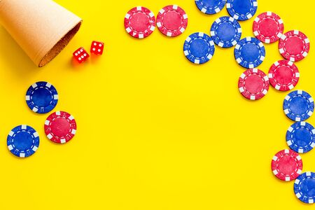 Poker frame. Chips and dices on yellow background top-down.
