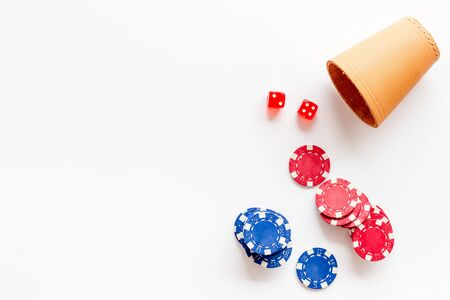 Poker concept. Chips, dices, cup for dice on white background top-down