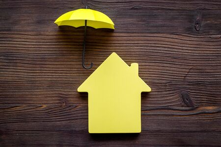 House insurance concept. Toy house defended by umbrella on dark wooden backgound top view.