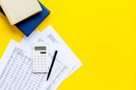 Financial literature. Books near documents, calculator on yellow background top-down copy space Stock fotó
