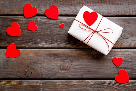 Valentines Day gift. Present box near paper hearts on dark wooden background top-down copy space