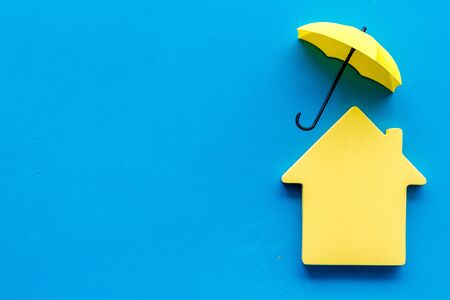 House insurance concept. Toy house defended by umbrella on blue backgound top view copy space