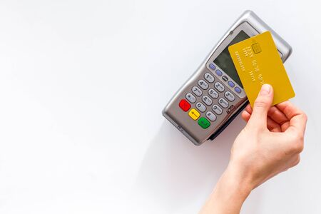 Contactless payment, paypass. Hand hold bank card near terminal on white background top-down copy space