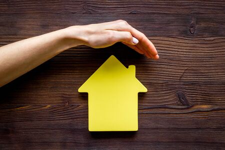 Property insurance concept. Hand defends house cutout on dark wooden backgound top view copy space