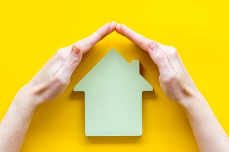 Property insurance concept. Hand defends house cutout on yellow backgound top view copy space