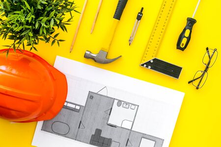 House building plan. Blueprints, instruments, helmet on yellow background top-down