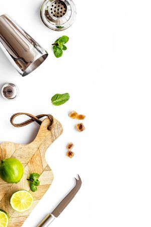 Bar background. Tools and ingredients for making cocktails. Shaker, lime on cutting board on white background top-down copy space