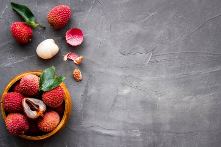 Fresh ripe lychee in bowl on grey desk top-down frame copy space