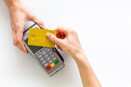 Pago sin contacto, paypass. Sostenga la tarjeta bancaria cerca de la terminal sobre fondo blanco de arriba hacia abajo.