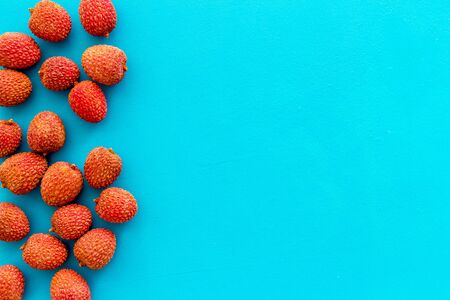 Lychee frame. Exotic asian fruits on blue background top-down copy space